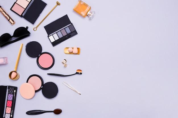 Palette di ombretti; spazzole ovali e polvere compatta; spugna; bottiglia di profumo; frizione e occhiali da sole su sfondo viola
