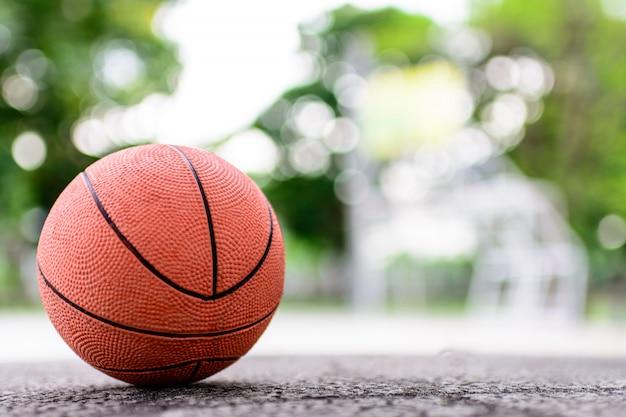Palla arancione per giocare a basket su un pavimento nel campo da basket al parco