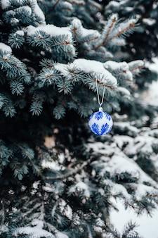 Palla blu di natale bianco sulla fine del ramo di albero dell'abete su