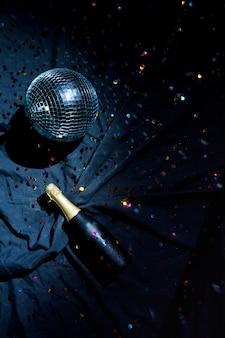 Palla da discoteca con bottiglia di champagne sul pavimento