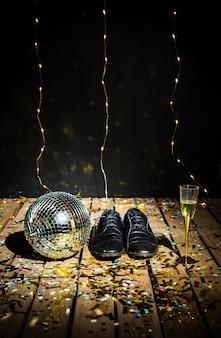 Palla da discoteca, stivali da uomo e bicchiere di bevanda tra i coriandoli