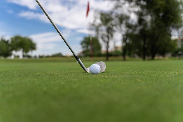 Palla da golf bianca e club di golf su un campo da golf