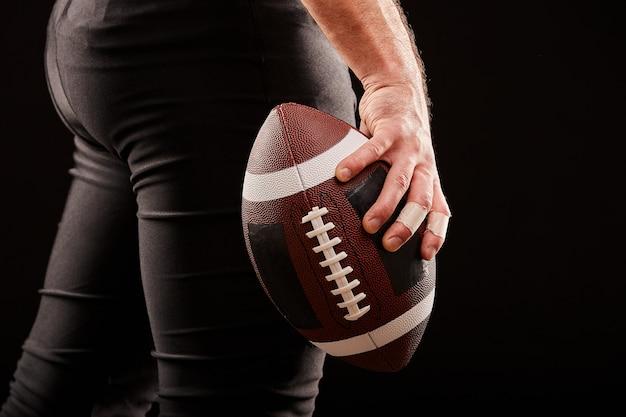Palla della tenuta del giocatore di football americano contro il cielo tenebroso