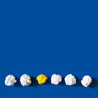 Palla di carta sgualcita giallo fra le palle bianche contro fondo blu