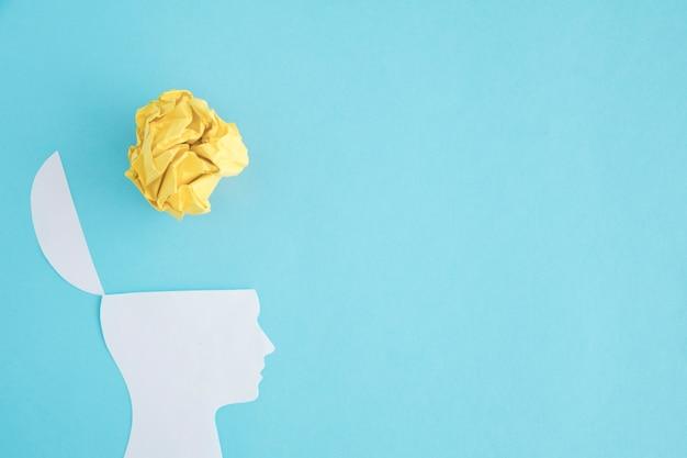 Palla di carta sgualcita giallo sopra la testa aperta sul contesto blu