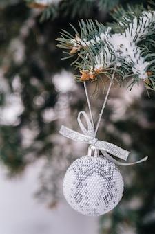 Palla di natale bianco argento sul ramo di un albero di abete si chiuda