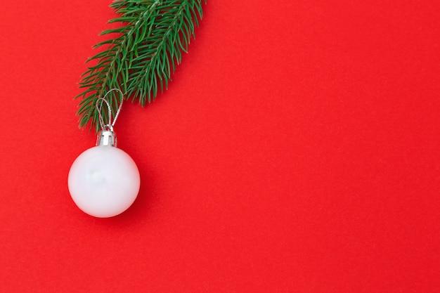 Palla di natale bianco sul ramo di un albero di natale sopra fondo rosso