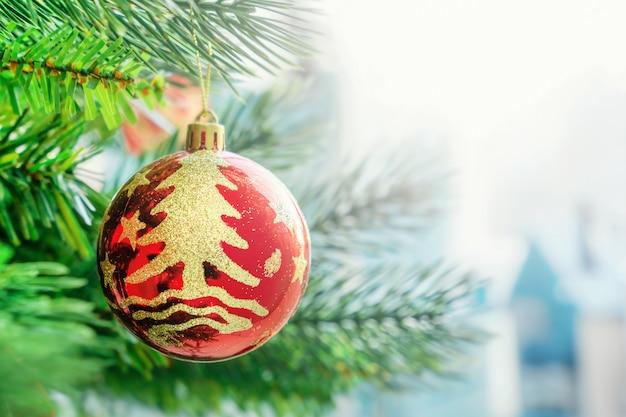 Palla di natale rossa, decorazione giocattolo, appesa al ramo verde dell'albero di natale.