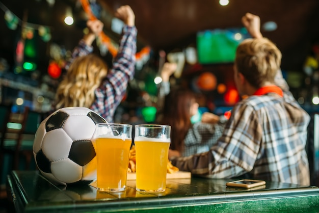 Palla e birra sul tavolo nel bar dello sport, tifosi di calcio