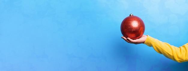 Palla rossa di natale a portata di mano su sfondo blu, concetto di buon natale
