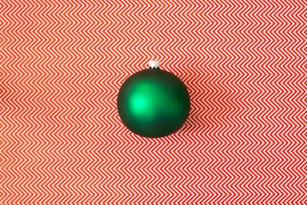 Palla verde dell'albero di natale su una parete astratta.