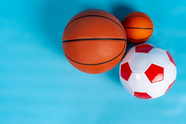 Pallacanestro e palloni da calcio su un fondo blu