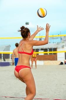 Pallavolo giocatore di spiaggia si prepara a servire la palla sulla spiaggia.