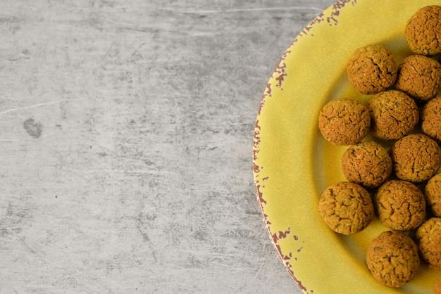 Palle al forno del falafel del cece sul piatto giallo su fondo grigio, alimento del vegano e sano con il tahini in profondità, il mediterraneo tradizionale, vista superiore, disposizione piana con lo spazio della copia