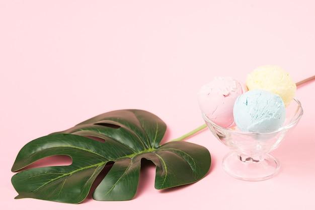 Palle del gelato sulla ciotola di vetro vicino alla foglia di monstera