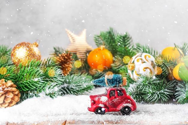 Palle di natale, mandarini e rami di un albero con un camion