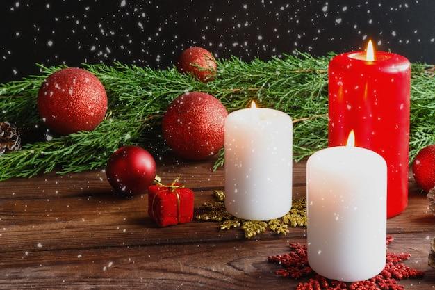 Palle di natale rosse, candele, rami di abete rosso, corona e fiocchi di neve su uno sfondo scuro