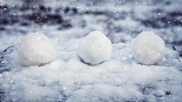 Palle di neve sul terreno innevato durante una nevicata