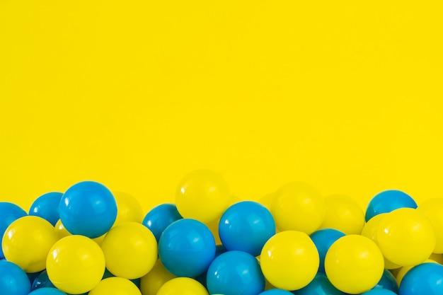 Palle di plastica gialle e blu in stagno della stanza del gioco