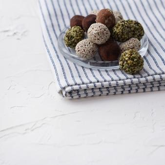 Palle dolci di energia cruda sana organica casalinga su un piatto con un tovagliolo.
