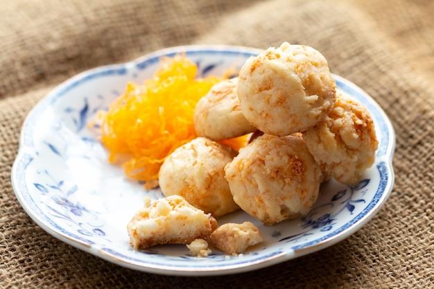 Palle dorate dei biscotti con le uova di seta per l'ora del tè nella mattina in piatto bianco