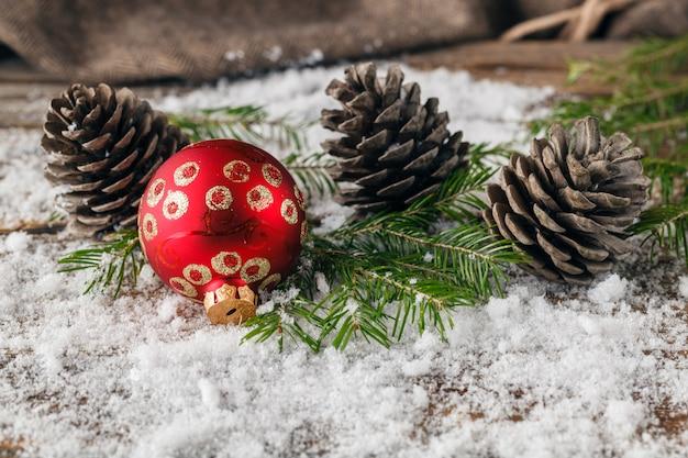 Palle rosse di natale con i ramoscelli e la pigna dell'abete sulla tavola della neve, fine su, spazio per testo, orizzontale