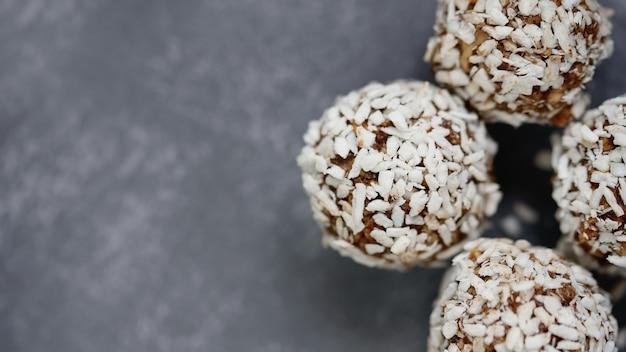 Palle sane di energia cruda con cacao, noce di cocco, sesamo, chia su fondo grigio.