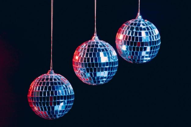 Palle scintillanti della discoteca che appendono nell'aria contro il fondo nero