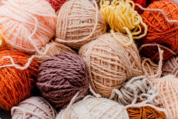 Palle variopinte di lana con i ferri da maglia su fondo bianco, sul hobby e sul concetto di tempo libero. filati per maglieria