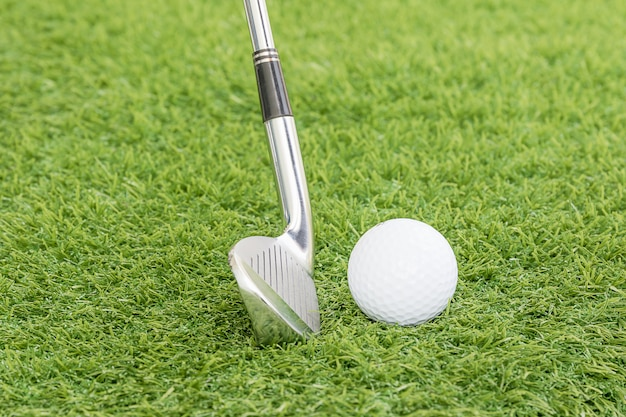 Pallina da golf e golf club sull'erba verde