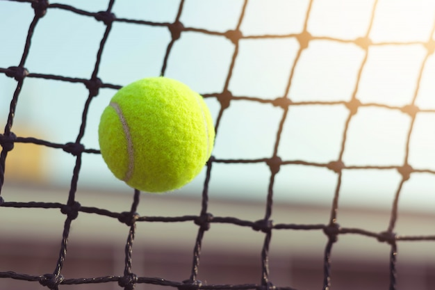 Pallina da tennis che colpisce alla rete sul fondo della sfuocatura della corte