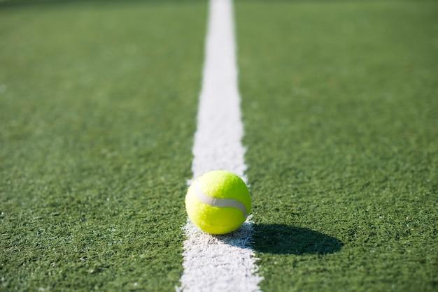 Pallina da tennis del primo piano su una linea di un campo da tennis