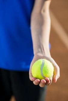 Pallina da tennis del primo piano tenuta a disposizione