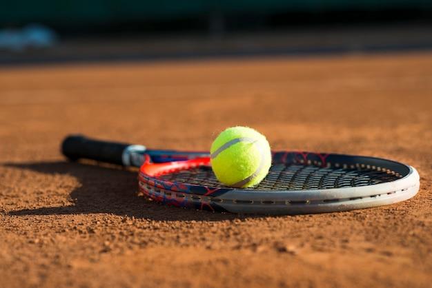 Pallina da tennis di primo piano su una racchetta posizionata sul pavimento