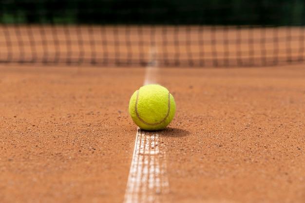 Pallina da tennis di vista frontale sulla terra del campo
