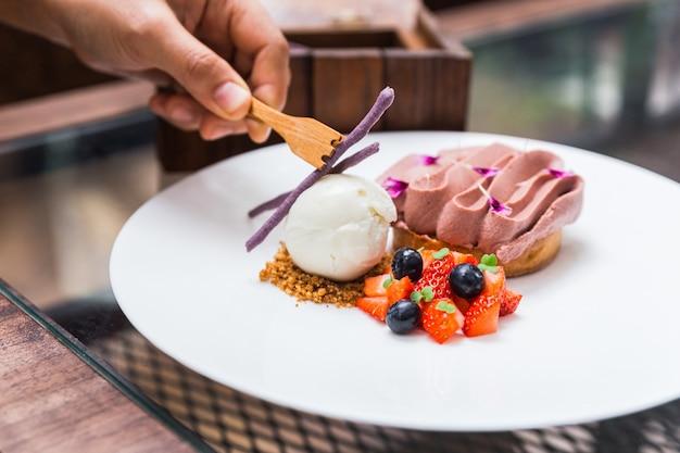 Pallina di gelato alla vaniglia e biscotto sbriciolato con alce al cioccolato e fetta di fragola e mora. decorato con piccoli fiori e bastoncini di taro viola.
