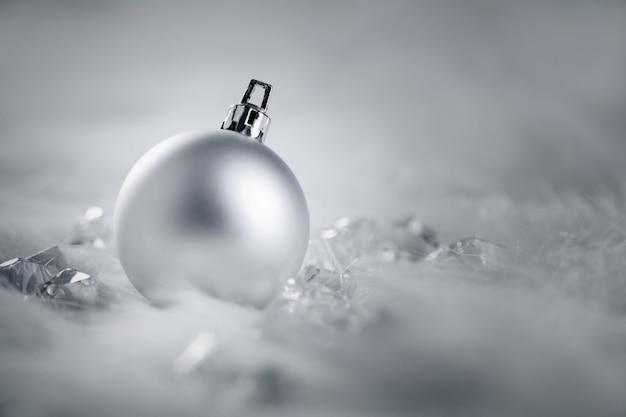 Pallina di natale argento su pelliccia neve e ghiaccio