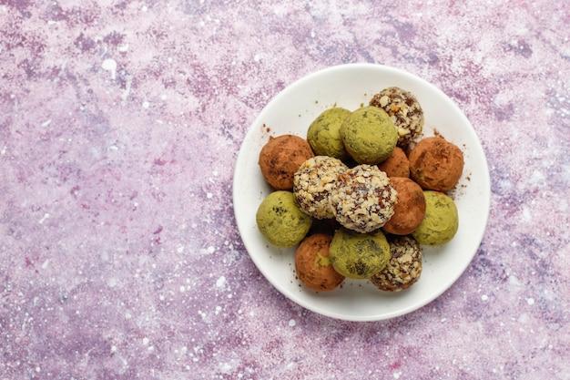 Palline al tartufo vegane sane fatte in casa con datteri e noci, polvere di matcha, cacao in polvere