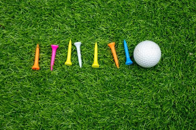 Palline da golf e tees sono su erba verde.