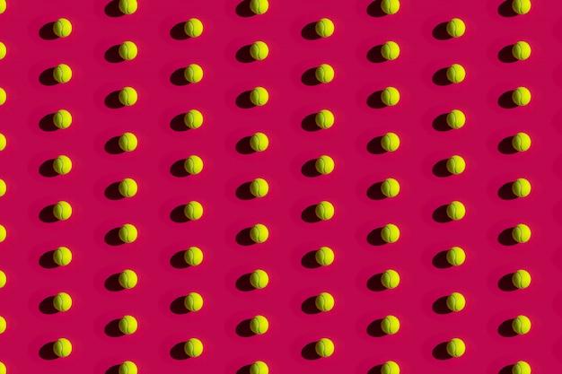 Palline da tennis con forti ombre su un rosa