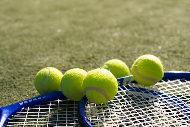 Palline da tennis del primo piano con le racchette