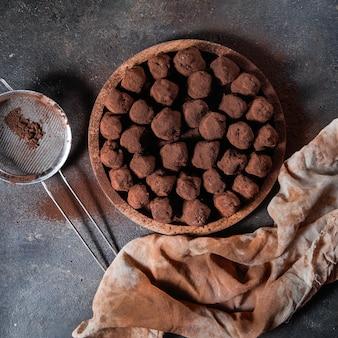 Palline di cacao in un piatto di legno con setaccio