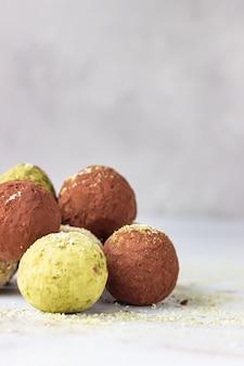 Palline di energia grezza con polvere di tè matcha, cacao in polvere e scaglie di cocco