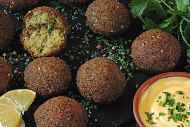 Palline di falafel, spezie, salsa ed erbe. falafel vegano. cibo sano e magro. cucina mediorientale.