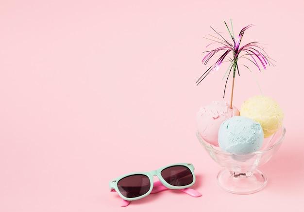 Palline di gelato con la bacchetta ornamentale sulla ciotola di vetro vicino agli occhiali da sole