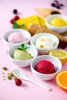 Palline di gelato in ciotole, coni di cialda, bacche, arancia, mango, limone, menta, pistacchio su rosa shabby chic. collezione colorata, concetto di estate