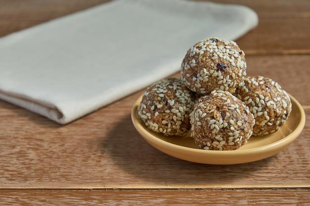 Palline di proteine di sesamo di farina d'avena. morsi di energia a basso contenuto di grassi con farina d'avena, noci di sesamo e prugne secche su legno