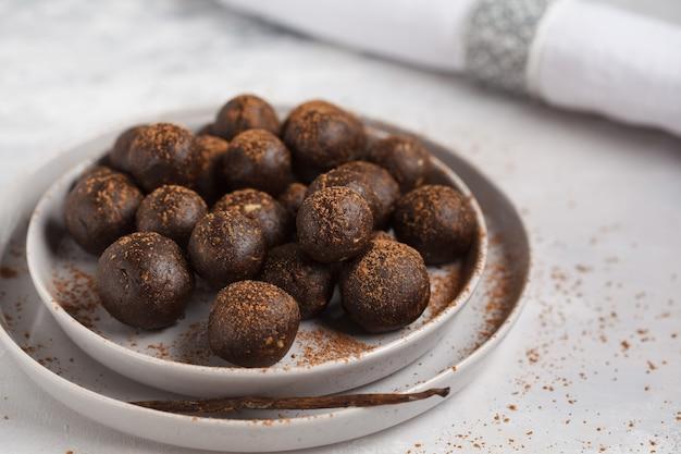 Palline dolci vegane crude alla vaniglia e cioccolato con noci, datteri e cacao. concetto di cibo sano vegan. sfondo grigio