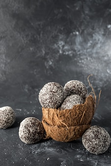 Palline sane fatte in casa di energia proteica in una ciotola di cocco con albicocche secche, uvetta, noci, mandorle e cocco. sano cibo dolce