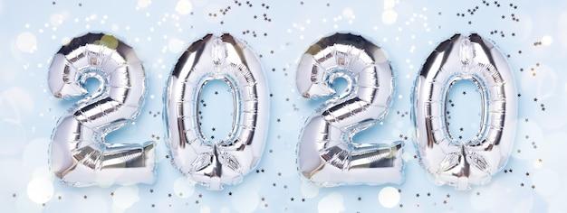 Palloncini d'argento sotto forma di numeri 2020 e coriandoli sul blu